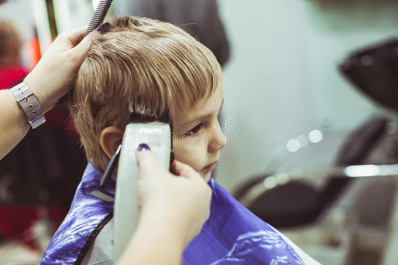 Little boy makes hairstyle at the hairdresser royalty free stock photo