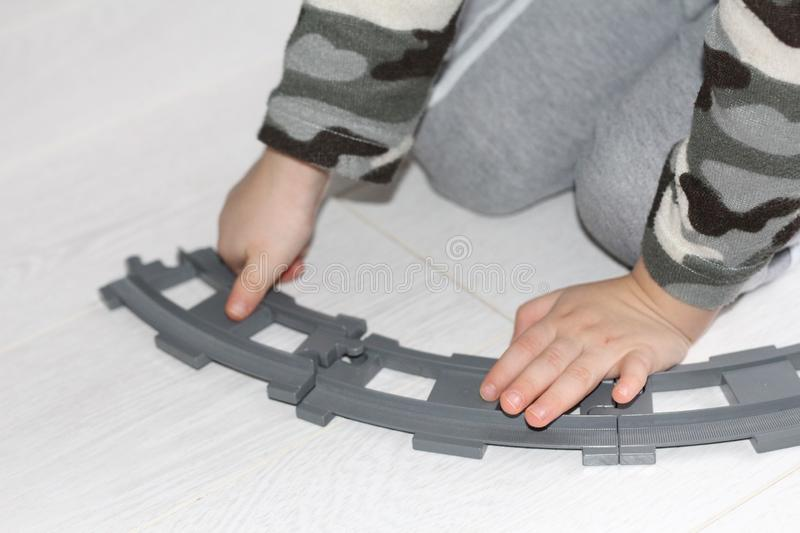 A little boy makes the railroad. The baby is playing stock image
