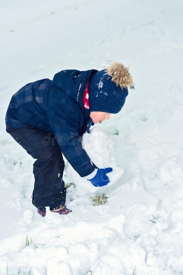 Little boy makes a snowman in winter. child rolls a snowball. happy kid plays and smiles. Emotion and happiness on children stock photo