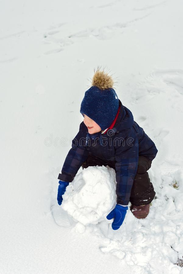 Little boy makes a snowman in winter. child rolls a snowball. happy kid plays and smiles. Emotion and happiness on children royalty free stock photo