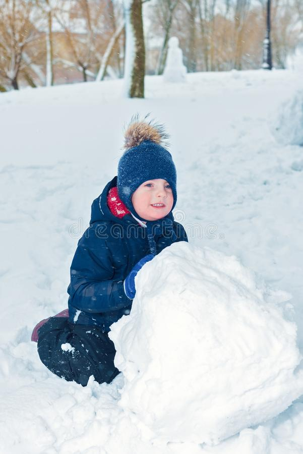 Little boy makes a snowman in winter. child rolls a snowball. happy kid plays and smiles. Emotion and happiness on children royalty free stock images