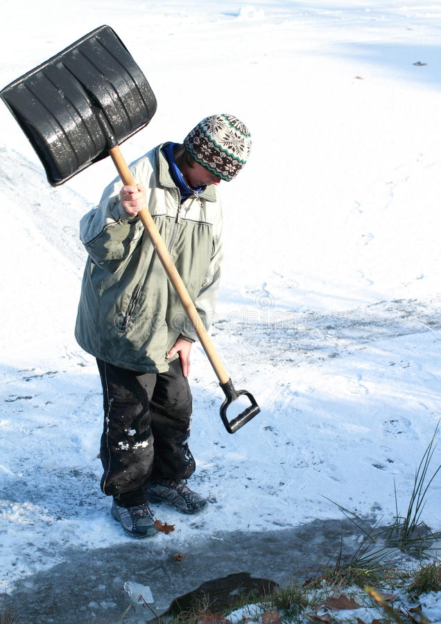 Download Little Boy Making A Hole In Ice On Pond Stock Photo - Image: 28102992