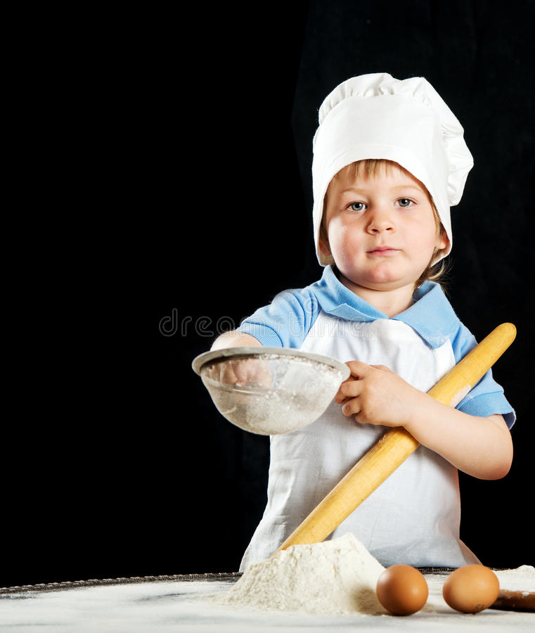 Little boy making pizza or pasta dough royalty free stock photography
