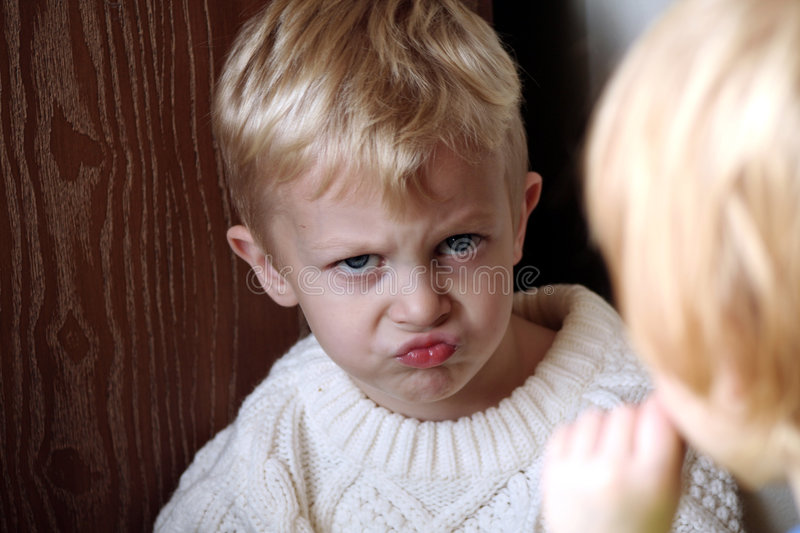 Little boy making pouting stock photography