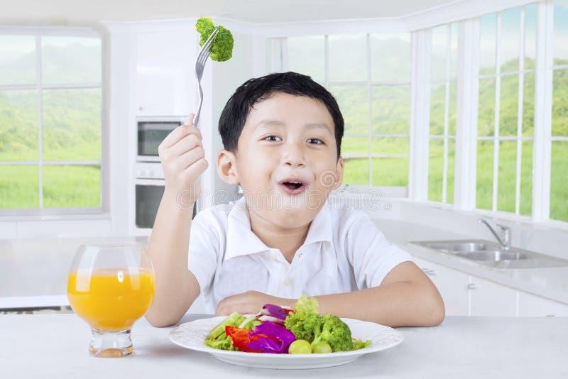 Little Boy mangeant de la salade végétale photo stock
