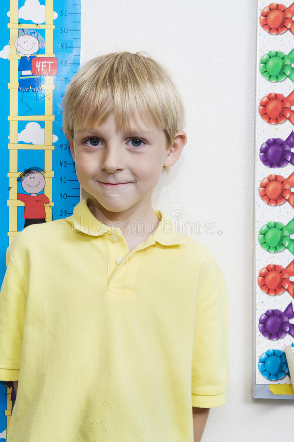 Download Little Boy Measuring Height In Classroom Stock Photo - Image: 29662620