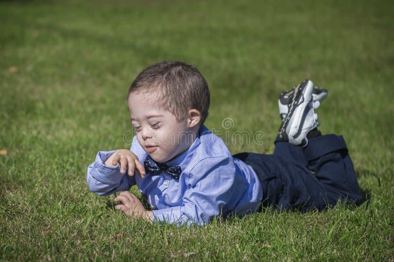 Little Boy med Down Syndrome som ligger på gräs arkivbild