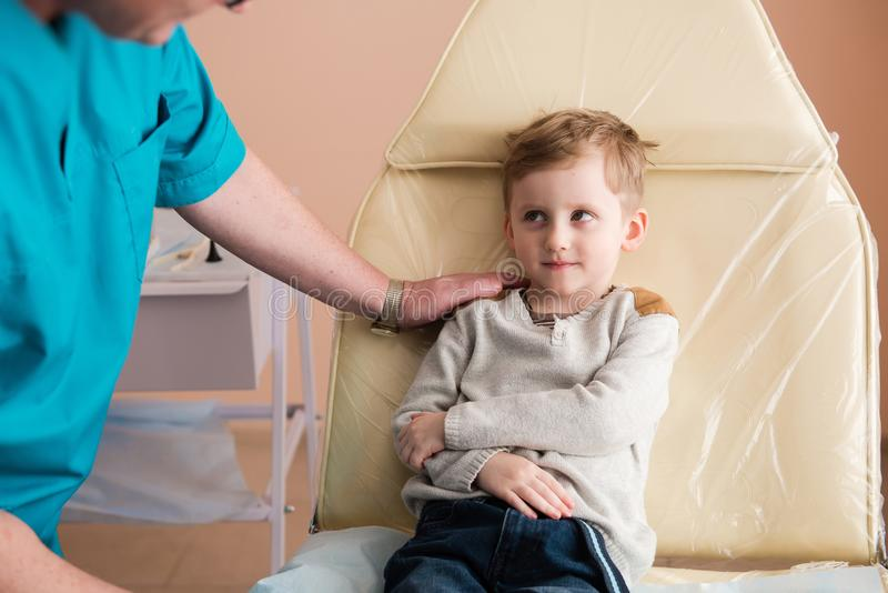 Little boy in medical chair. Kid in clinic and doctor put hand on his shoulder. Little boy in medical chair royalty free stock photo