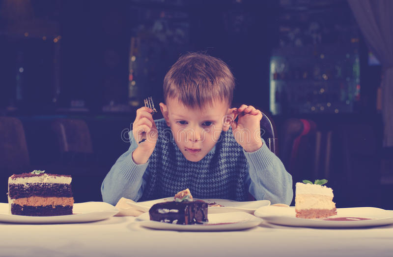 Little boy mesmerised by an assortment of cakes. Funny little boy mesmerised assortment cakes displayed dining table front him tries make choice where begin royalty free stock photos