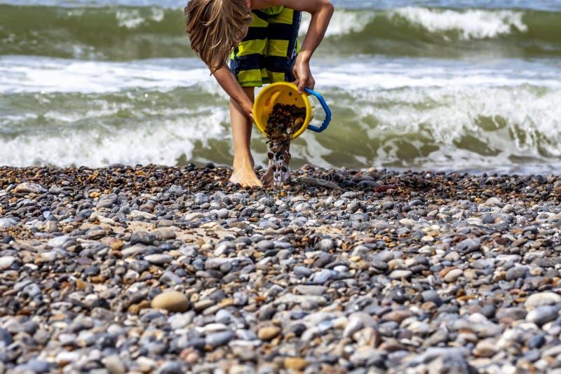 Little Boy met Emmer het spelen met stenen en zand bij het strand royalty-vrije stock afbeeldingen