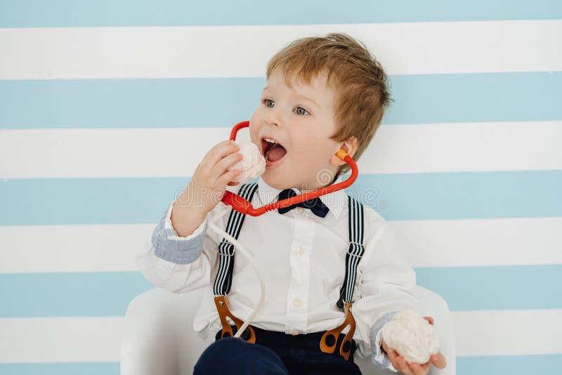 Little Boy met Toy Stethoscope Eating Marshmallow royalty-vrije stock afbeelding