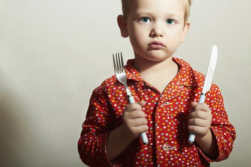 Little Boy met Vork en Knife.Want om te eten stock foto