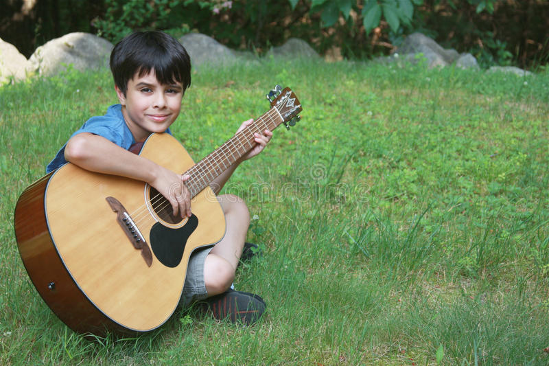 Little Boy mignon jouant la guitare images stock
