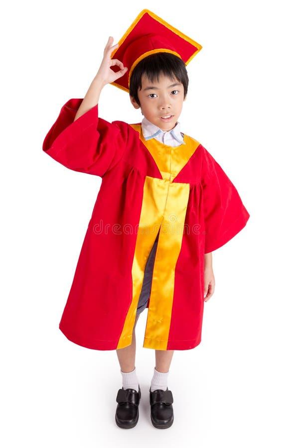 Little Boy mignon portant l'obtention du diplôme rouge d'enfant de robe avec la taloche photos libres de droits
