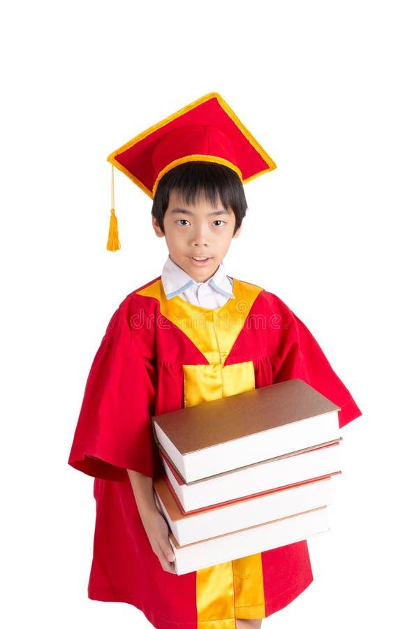 Little Boy mignon portant l'obtention du diplôme rouge d'enfant de robe avec la taloche image stock