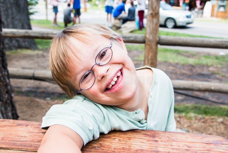 Little Boy mit dem Abstieg-Syndrom, das bei Tisch sitzt stockfotos
