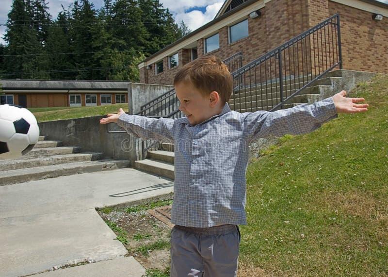 Little Boy mit Fußball-Kugel-mittlerer Luft stockbild
