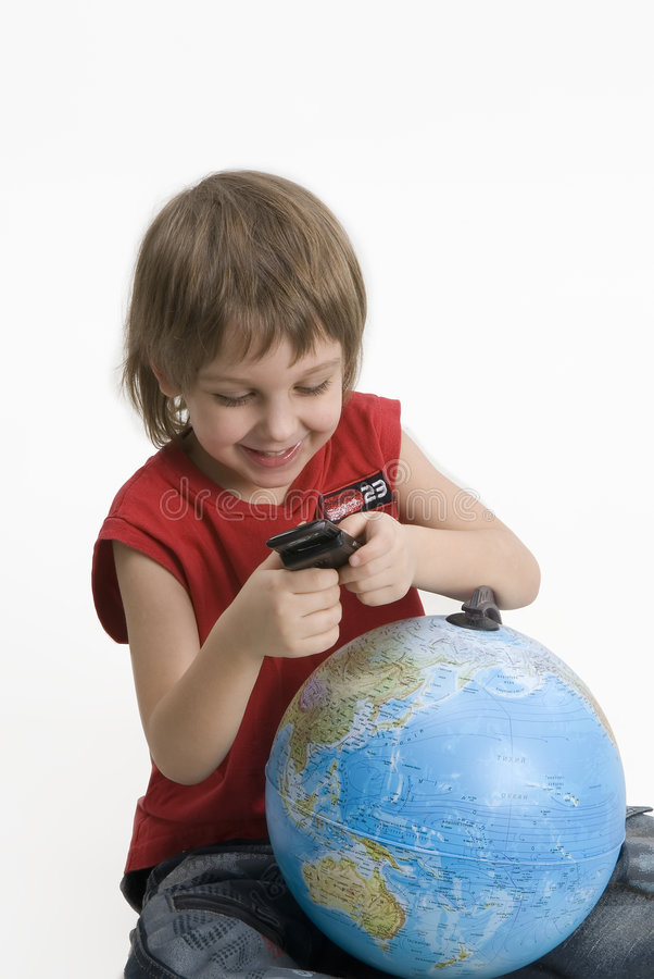 Little boy with a mobile phone and a globe royalty free stock photo