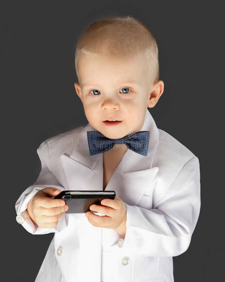 Little boy with the mobile phone. Kid in a white suit holds the mobile phone in hand royalty free stock photography