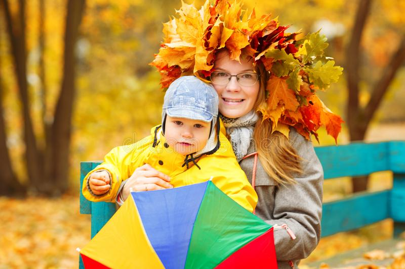 Little boy with mother on background of autumn park. Child and m. Om with a maple leaf. Family fall scene stock photos