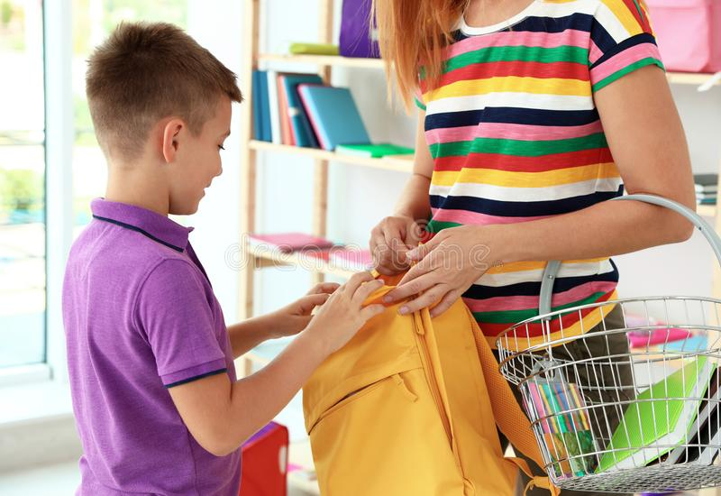 Little boy with mother choosing school backpack in shop stock photos