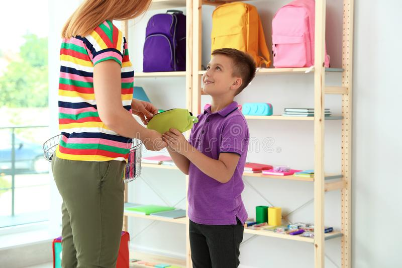 Little boy with mother choosing school stationery stock images