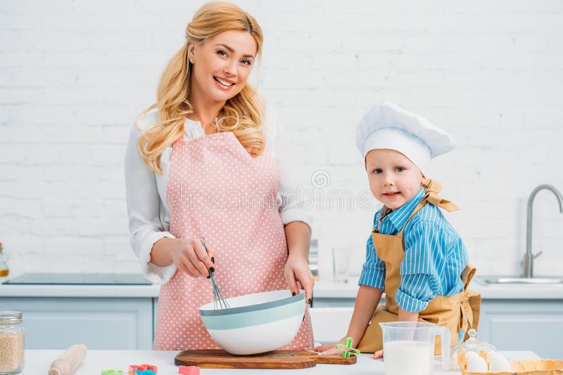 Little boy and mother cooking together royalty free stock photography