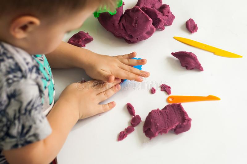 Little boy moulds from plasticine on table, Child hands playing with colorful clay. stock photography