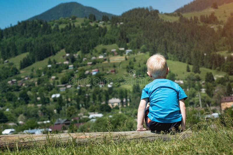 Little boy on mountains background. Weekend in nature with child. Back view royalty free stock photo