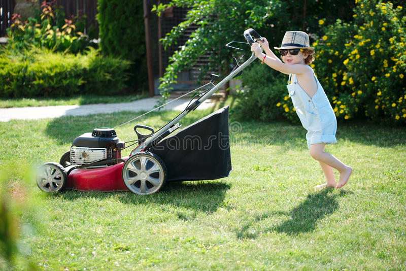 Little boy mows lawn with mower stock photography