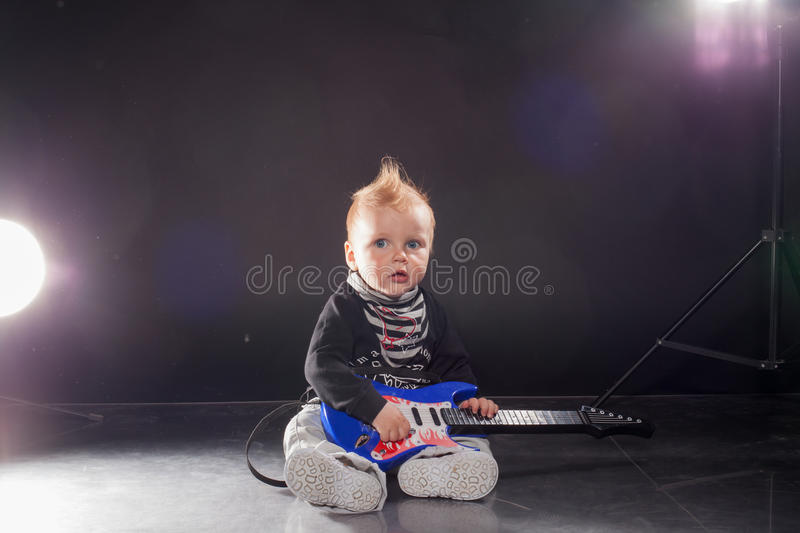 Little boy musician playing rock music on the guitar royalty free stock photography