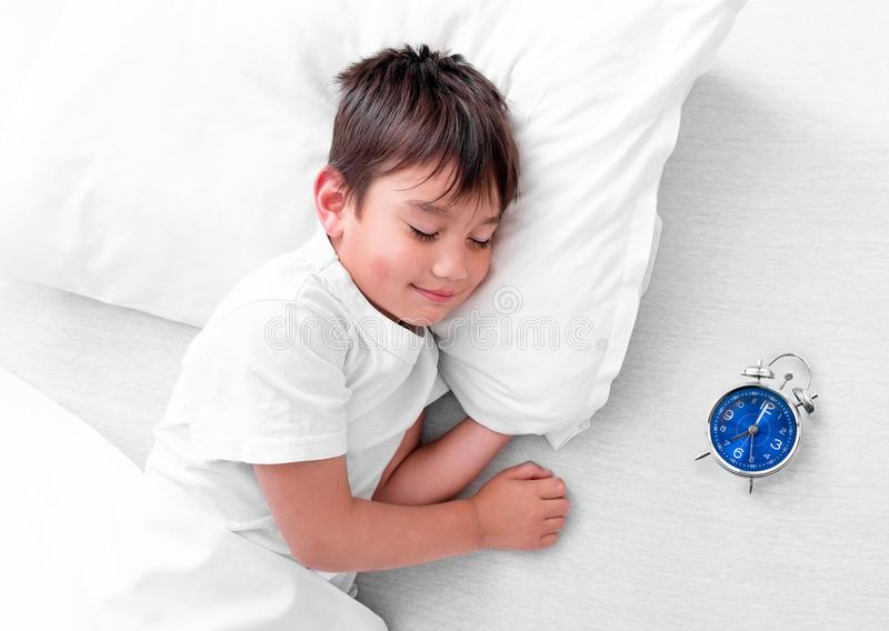 Little boy sleeping in white bed with small alarm clock. Little boy napping while lying on his side in white bed with small alarm clock near him royalty free stock images