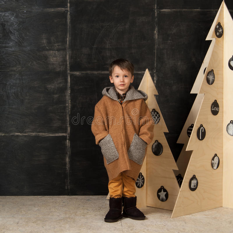 The little boy next to decorative Christmas trees stock image