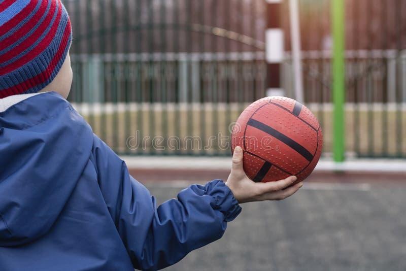 Little Boy, niño del niño en una chaqueta azul y un sombrero sostiene una bola en una mano, colocándose en el campo con una meta  fotos de archivo libres de regalías