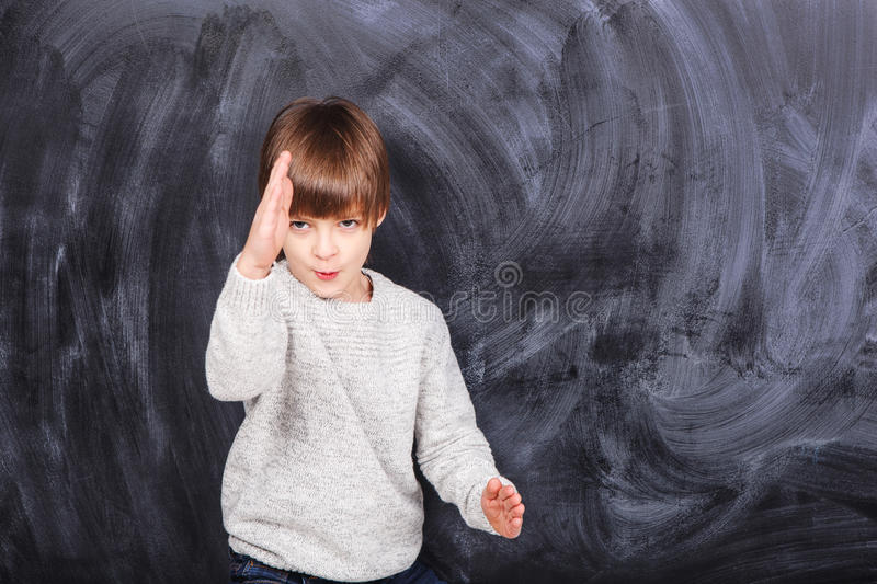 Little boy ninja. Very handsome boy on a gray background in a gray jacket. In the photo you can to finish anything stock photography