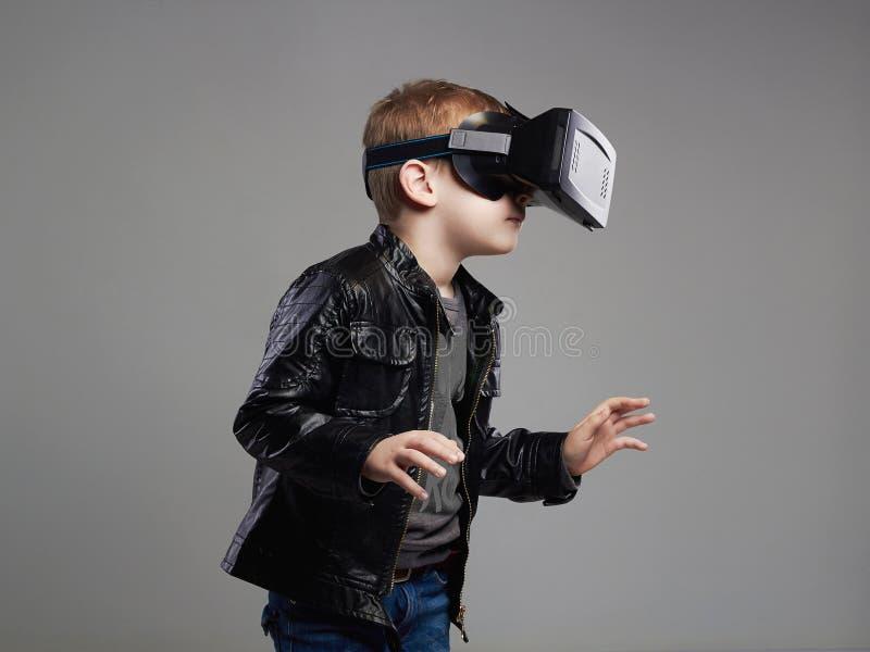 Little Boy nos vidros da realidade virtual que jogam o jogo Caçoa o divertimento imagem de stock