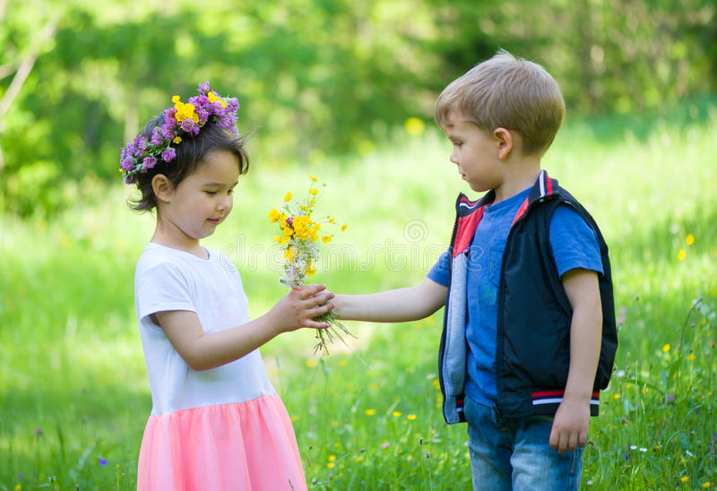 Little boy offering flowers to a little girl stock images