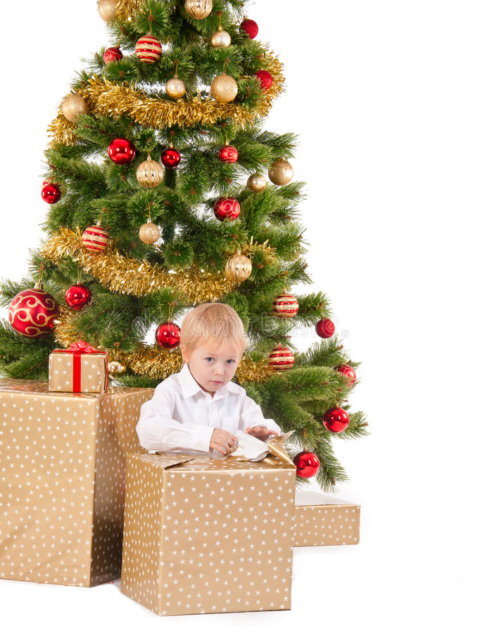 Little boy opening Christmas gift near New Year's tree royalty free stock photography
