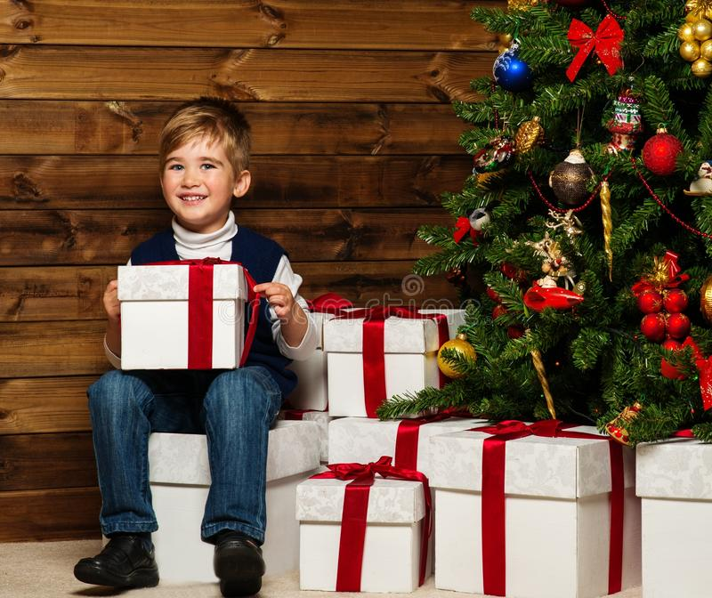 Little boy opening gift box under christmas tree. Little boy with gift box under christmas tree in wooden house interior stock photography