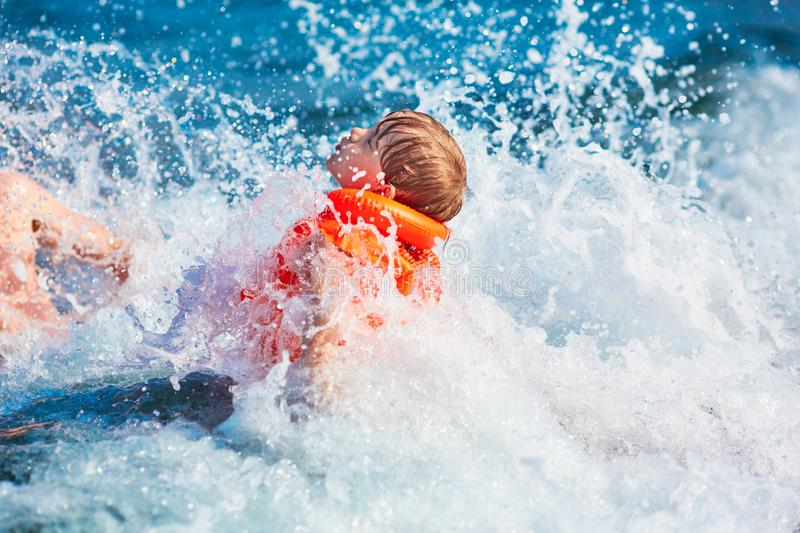 Little boy in orange life jacket swimming in the sea with waves with big splashes. Selective DOF royalty free stock images