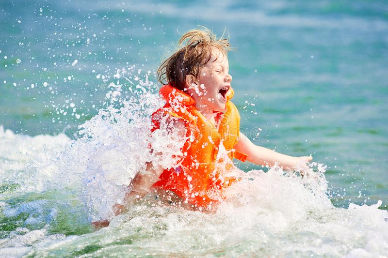 Little boy in orange life vest swimming in wave sea royalty free stock images
