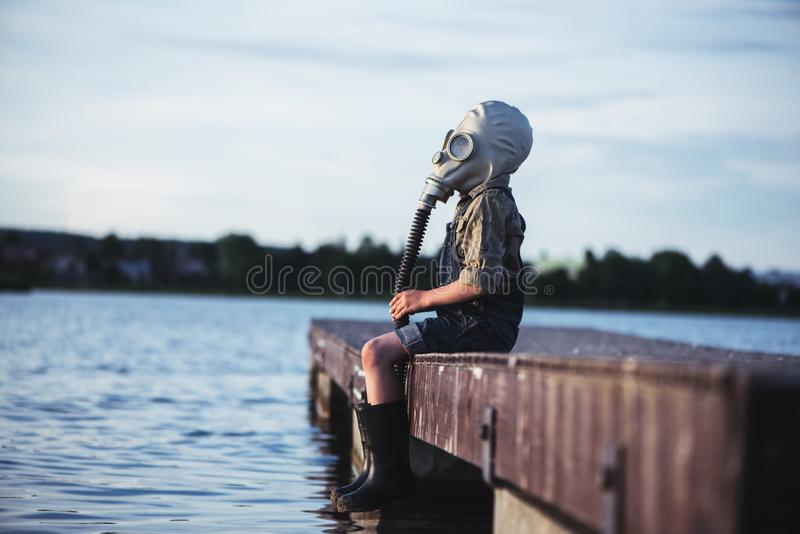 Little boy over the water in a gas mask royalty free stock photos