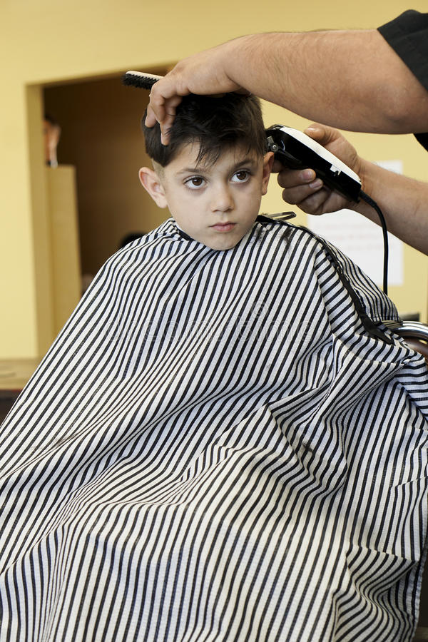 Little Boy på Barber Shop Getting en frisyr royaltyfri fotografi