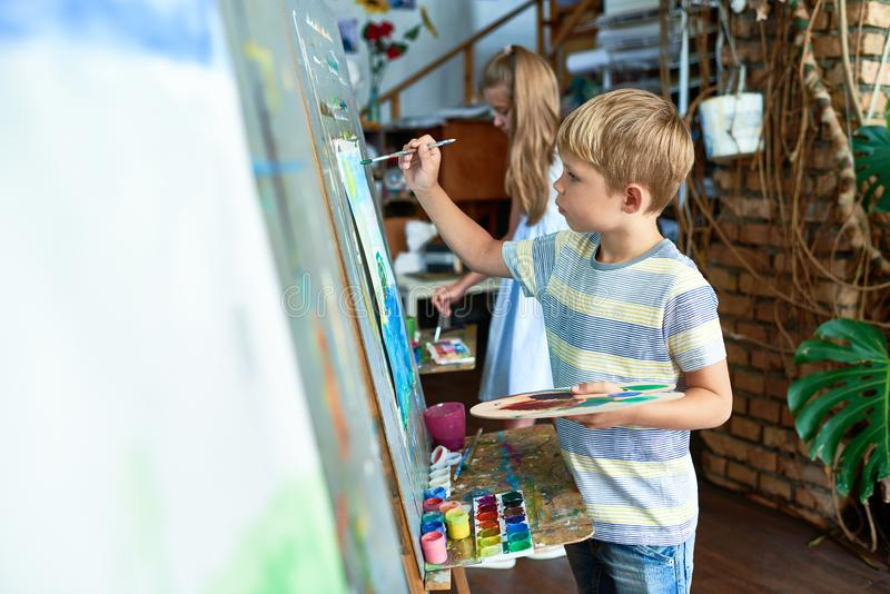 Little Boy Painting in Art Class. Side view portrait of blonde little boy painting on easel in art class with other children in background royalty free stock photo
