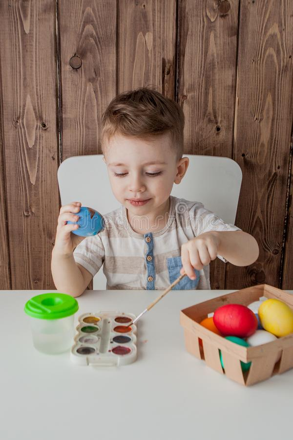 Little boy painting colorful eggs for easter on wooden background.  stock images