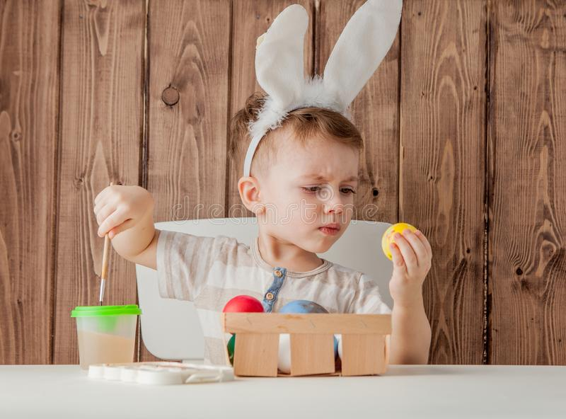Little boy painting colorful eggs for easter on wooden background.  stock photo