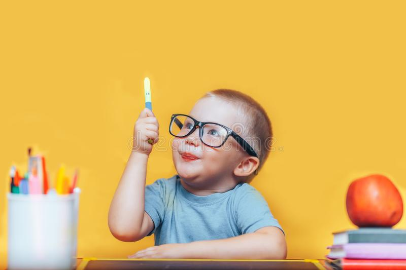 Little boy painting and doing homeworks on his desk having an idea, inspiration concept. back to school on yellow background.  royalty free stock image