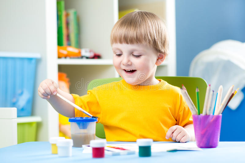 Little Boy Painting. In kindergarten or daycare center royalty free stock photography