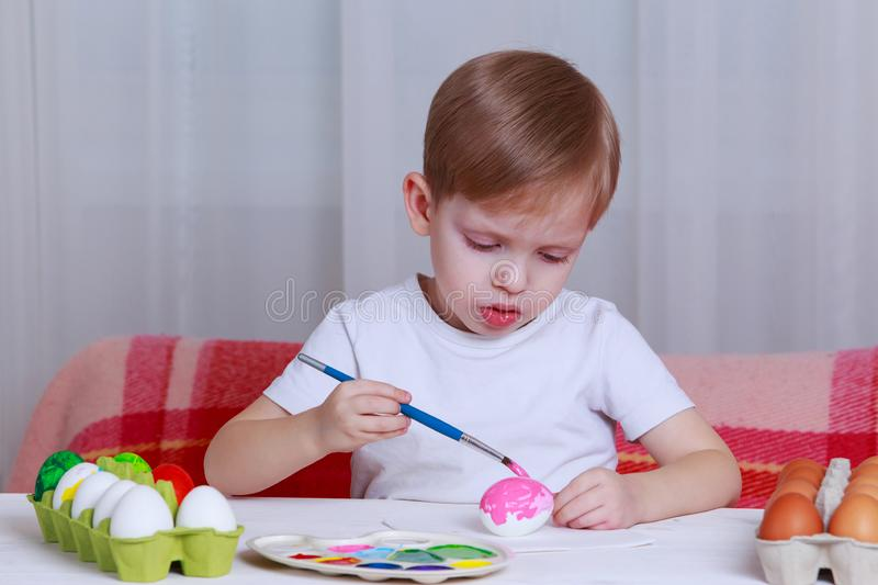 Little boy paints eggs stock images