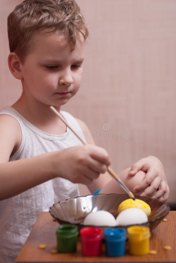 A little boy paints the eggs on the eve of Easter, colorful paints and brush, royalty free stock images